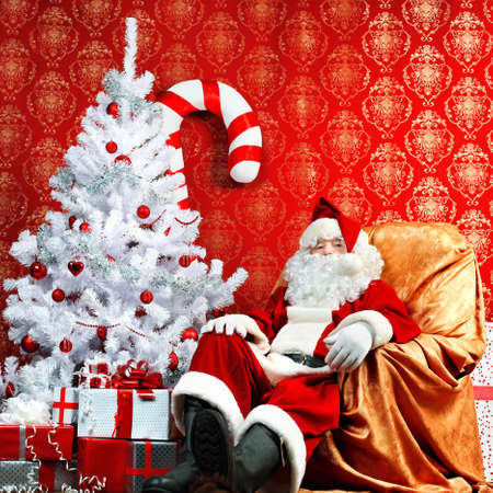 Santa Claus with presents and New Year tree at home. Christmas. photo