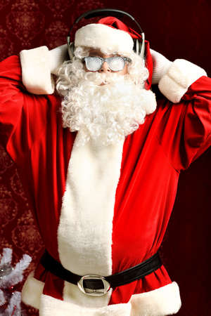 audifonos dj: Santa Claus es escuchar música en auriculares. Navidad. Foto de archivo