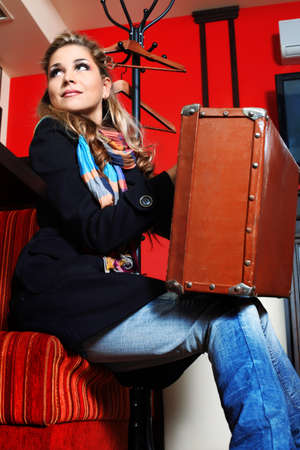 caf: Beautiful young woman traveller with an old suitcase at a caf Stock Photo