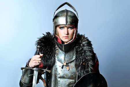 Portrait of a medieval female knight in armour over grey background. photo