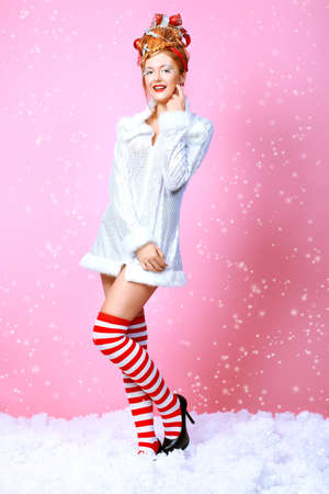 Fashionable young woman in Christmas clothes over pink background. Stock Photo - 8492925