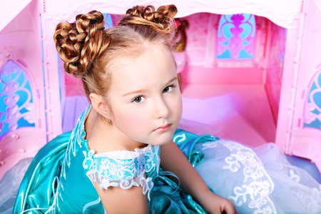 Beautiful little girl in princess dress playing with her toy castle. photo
