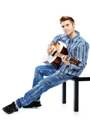 Handsome young man musician playing his guitar. Isolated over white background. photo