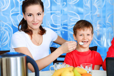 Happy mother with her son having a dinner at home. photo