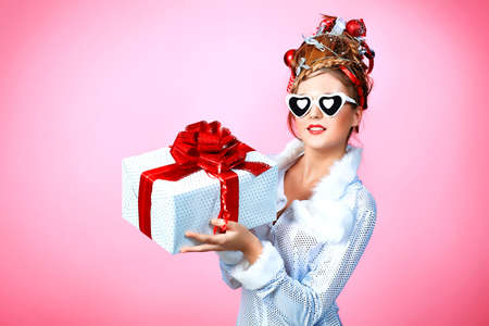 Beautiful young woman in Christmas clothes over pink background. Stock Photo - 8506903
