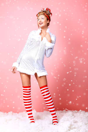 Fashionable young woman in Christmas clothes over pink background. Stock Photo - 8506900