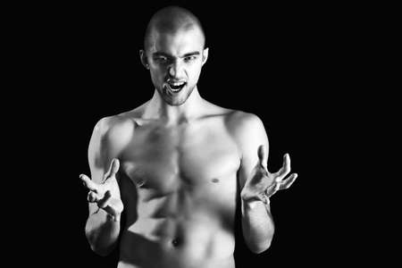 skinhead: Portrait of a handsome muscular man posing over black background.