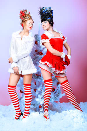 Two beautiful young women in Christmas clothes posing with New Year tree. photo