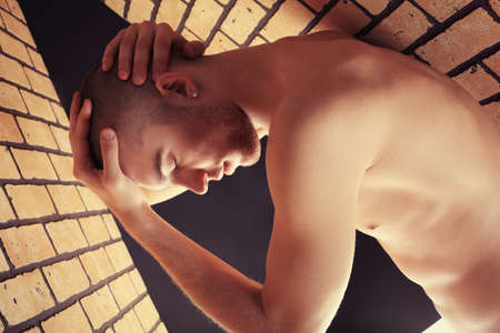 hairless: Portrait of a muscular man posing in a closed space over black background and brick wall.