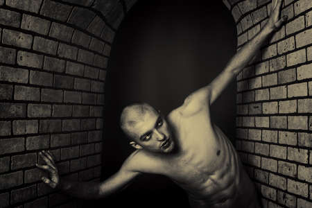 claustrophobia: Portrait of a muscular man posing in a closed space over black background and brick wall.