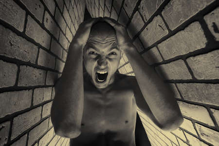 claustrophobia: Portrait of a handsome muscular man posing over black background and brick wall. Stock Photo