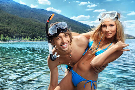 Happy young couple with snorkelling gear standing on a sea beach. photo