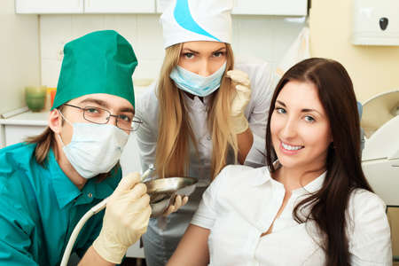 Shot of a young woman with dentists in a dental surgery. Healthcare, medicine. photo