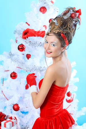 Beautiful young woman in Santa Claus clothes posing over Christmas background. photo