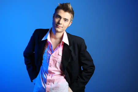 Young man dressed in rocknroll style, posing over blue background. photo