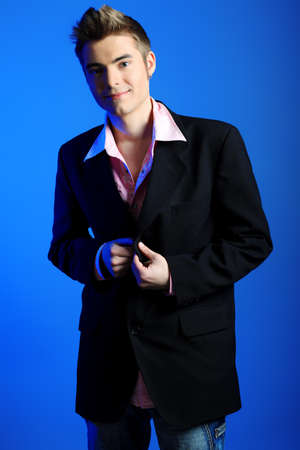 fop: Young man dressed in rocknroll style, posing over blue background.