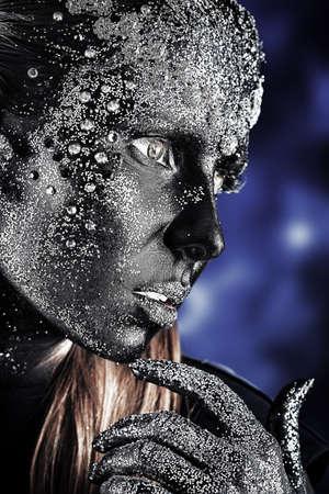 Portrait d'une femme artistiques peint avec la couleur noire et pailletée. Projet de peinture corporelle. Bijoux.
