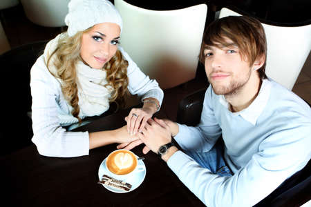 Happy couple of young people having a date at a caf photo
