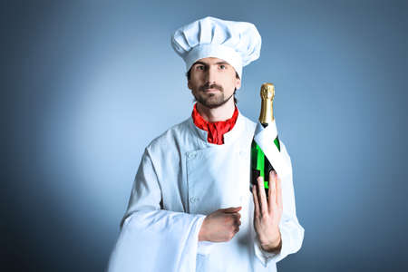 Portrait of a man cook holding a bottle of champagne. Shot in a studio over grey background. photo