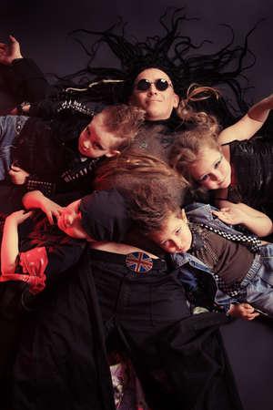 harmonist: Heavy metal musician  with children lying on a floor. Shot in a studio.