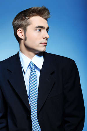 Portrait of a young businessman posing over grey background. photo