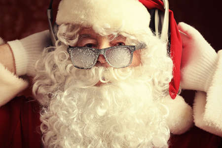 Santa Claus is listening to music in headphones. Christmas. Stock Photo - 8646632
