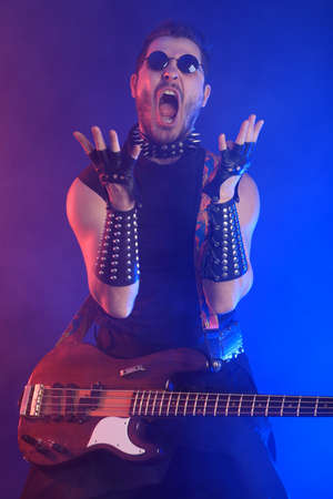 Heavy metal musician  is playing electrical guitar. Shot in a studio. Stock Photo - 8646616