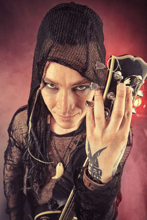 Heavy metal musician  is playing electrical guitar. Shot in a studio. Stock Photo - 8646639
