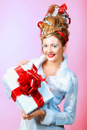 Beautiful young woman in Santa Claus clothes holding a present over pink background. photo