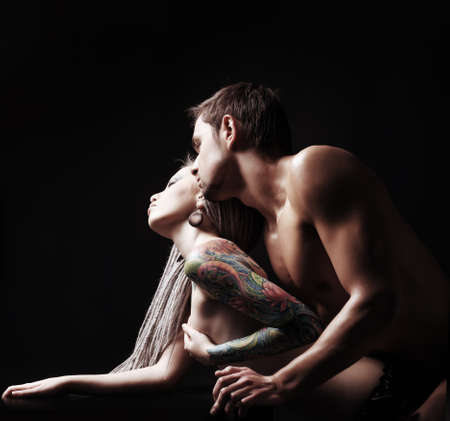 naked girl black hair: Shot of a passionate loving couple. Over black background.