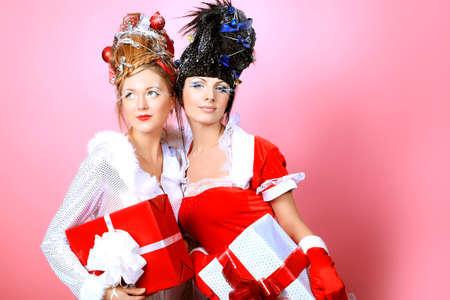Dos hermosas mujeres jóvenes en ropa de Navidad posando sobre fondo de color rosado. Foto de archivo
