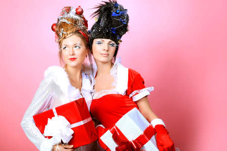 Two beautiful young women in Christmas clothes posing over pink background. Stock Photo - 8646690
