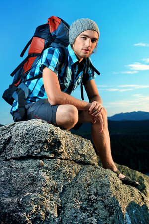 adventure sports: Young man tourist is sitting at the top of a mountain with a feeling of freedom.