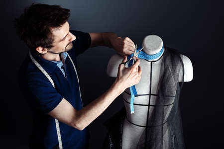 textile designer: Portrait of a man fashion designer working with dummy at studio. Stock Photo