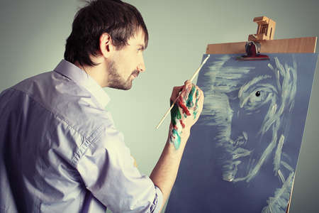 creative pictures: Portrait of an artist painting on easel. Shot in a studio.