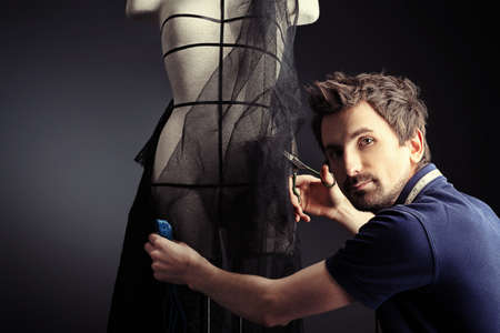 dressmaker: Portrait of a man fashion designer working with dummy at studio. Stock Photo