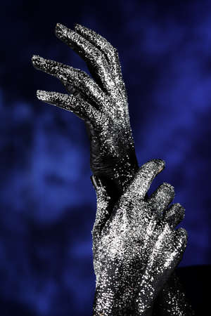 Portrait of an artistic woman painted with black color and spangled. Hands. photo