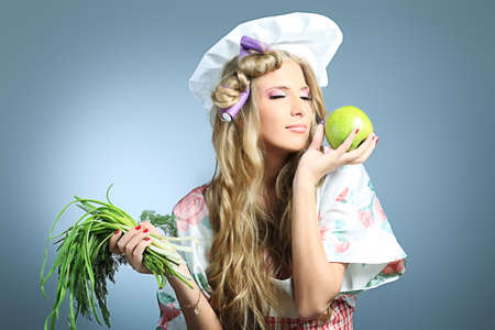 Beautiful blonde woman housewife holding greens and fruits. Studio shot over grey background. Stock Photo - 8714130