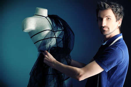haute couture: Portrait of a man fashion designer working with dummy at studio. Stock Photo