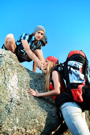 Couple of tourists are standing at the top of a mountain with a feeling of freedom. Stock Photo - 8751072