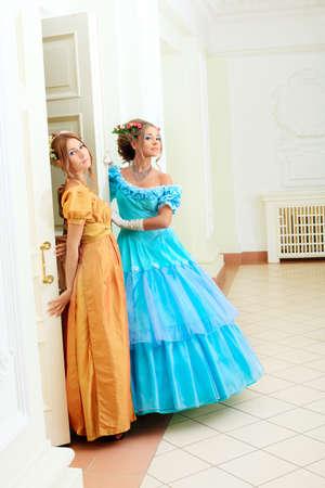 Two beautiful women in medieval era dresses. photo