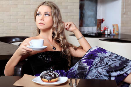 Beautiful young woman with a cup of tea at a caf photo