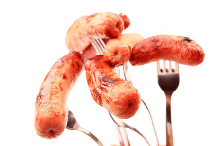 Close-up of fried sausages  on forks. Isolated over white background. photo