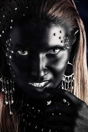 Retrato de una mujer artística pintada de color negro y spangled. Proyecto de pintura del cuerpo. Joyería.