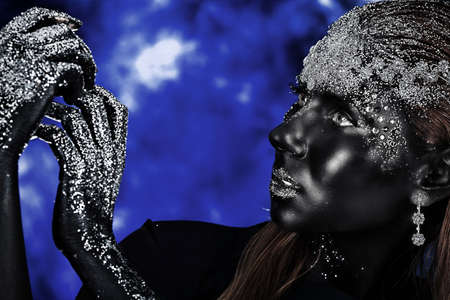bodypainting: Portrait of an artistic woman painted with black color and spangled. Body painting project. Jewellery.