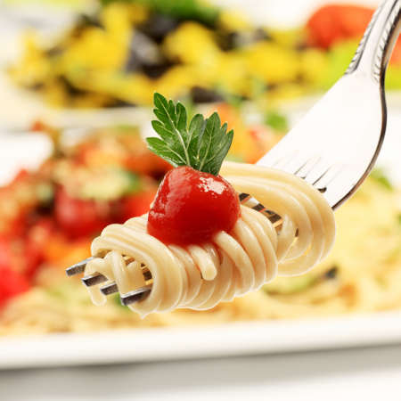 pasta dish: Close-up of a fork with spaghetti over pasta dishes.