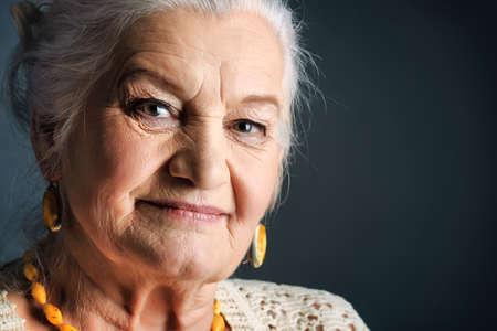 ancianos felices: Retrato de una mujer sonriente senior. Studio dispar� sobre fondo gris.