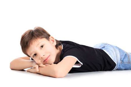 Portrait of a happy 9 year boy lying on a floor. Isolated over white background. Stock Photo - 8834966