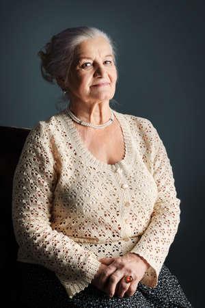 grandmas: Retrato de una mujer sonriente senior. Studio dispar� sobre fondo gris.