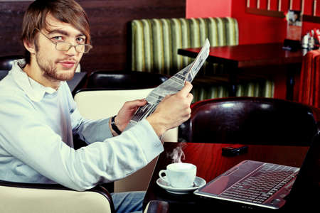 Handsome young man with a cup of tea reading a newspaper at a caf photo